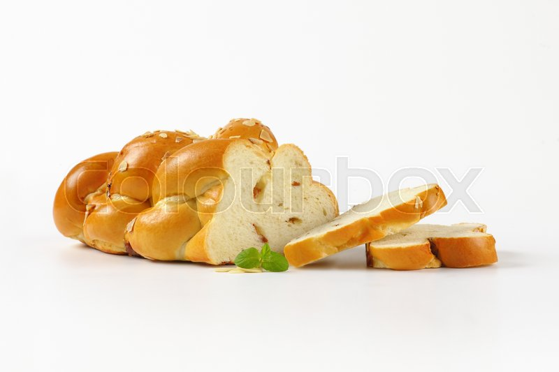 Stock image of 'sliced sweet braided bread on white background'
