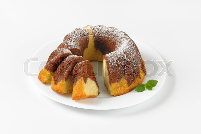 Stock image of 'partially sliced marble bundt cake on white plate'