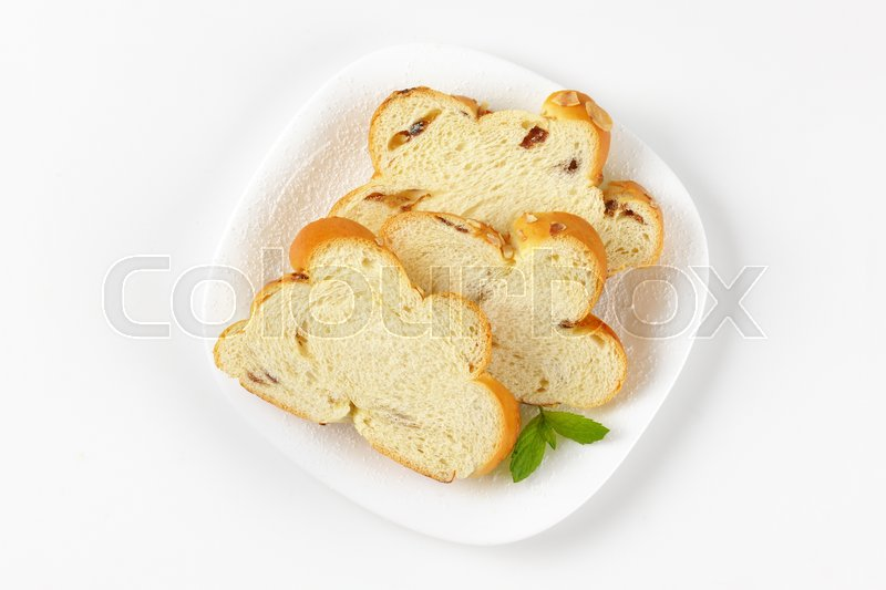 Stock image of 'slices of Christmas sweet braided bread with almonds and raisins'