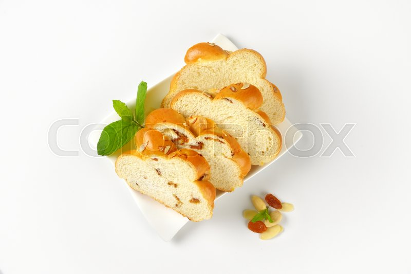 Stock image of 'slices of sweet braided bread with almonds and raisins on white plate'