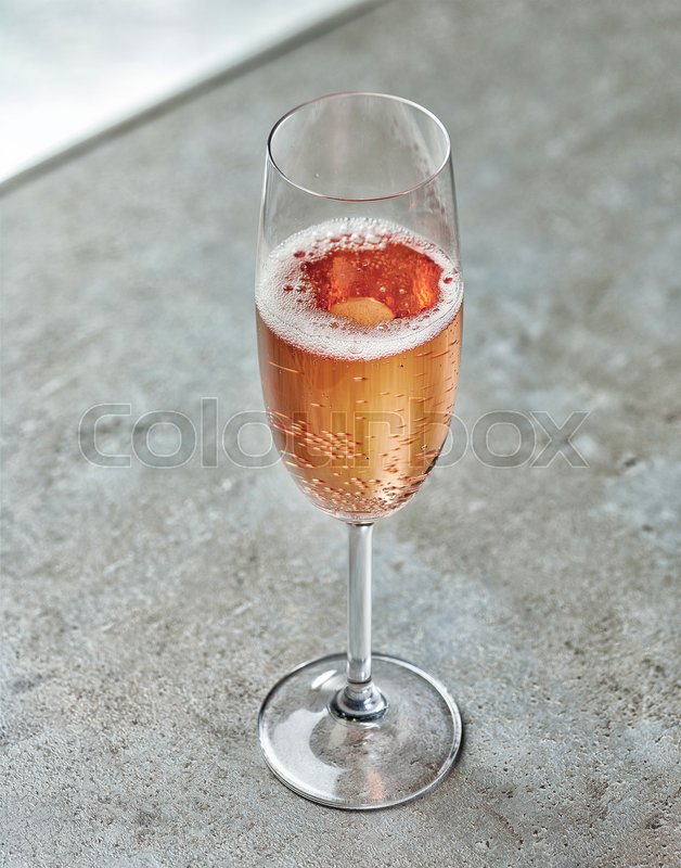 Stock image of 'glass of pink champagne on grey table'