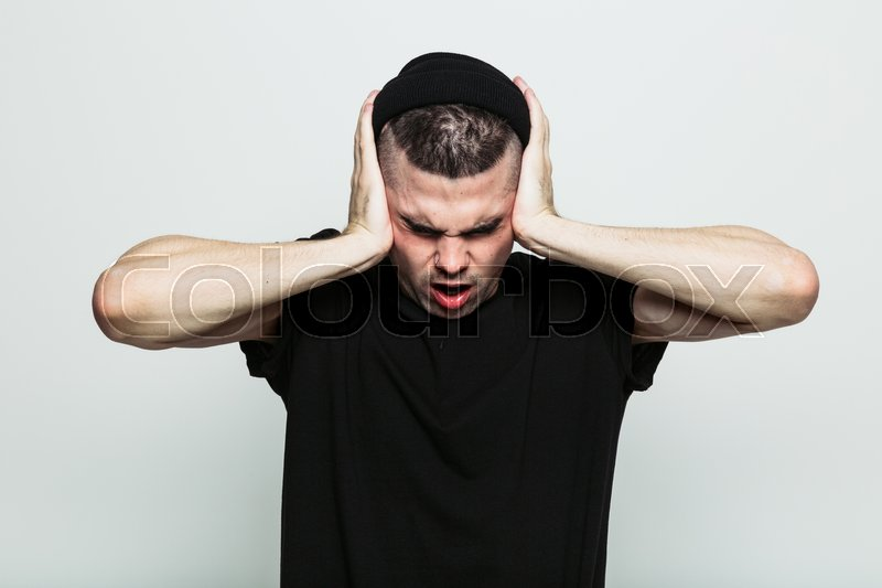 Stock image of 'Man in black t-shirt against grey studio background that doesn't want to hear anything from you'