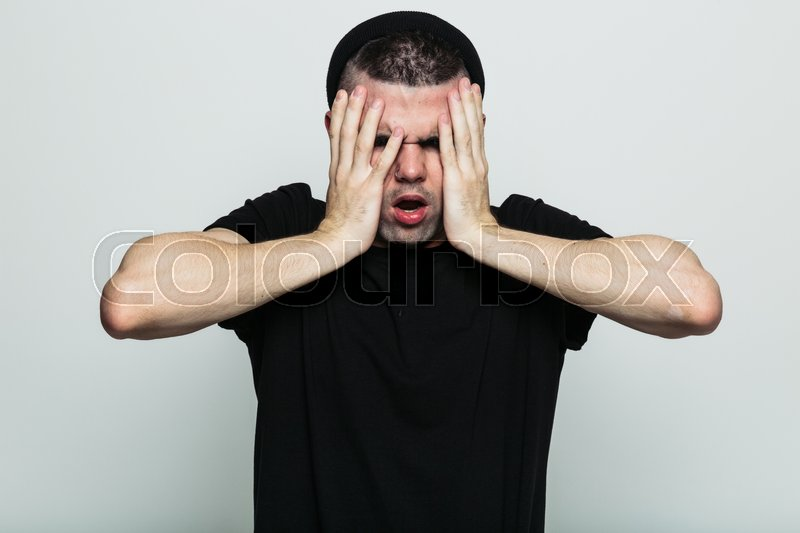 Stock image of 'Expressive portrait of young man screaming with hands on face. White studio background.'