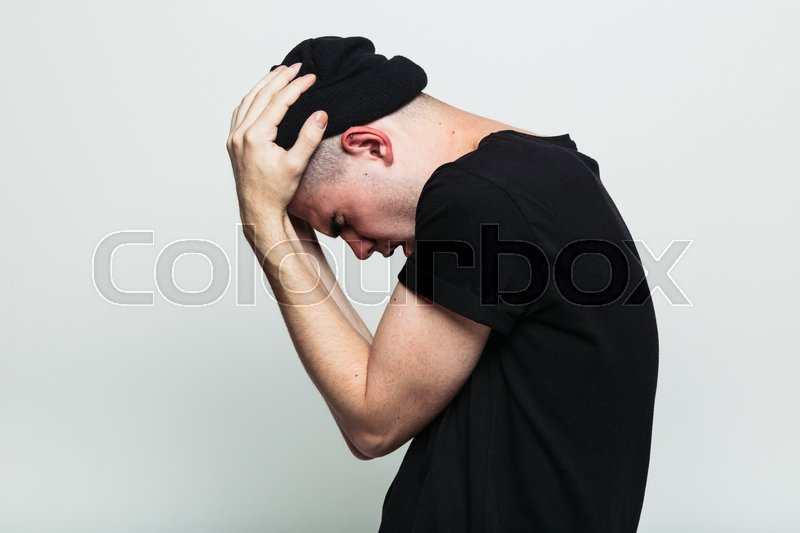 Stock image of 'Side view of young man in stress pose on white background with hands on head. Studio shot.'