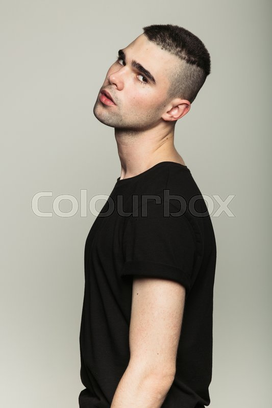 Stock image of 'Studio shoot of young man wearing black t-shirt turned away and looking at camera. Side view.'