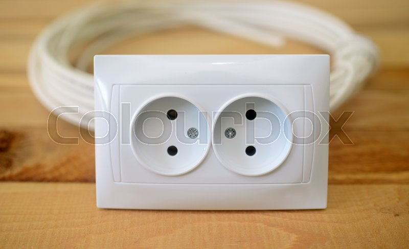 Stock image of 'coil of electrical cable and outlet on wooden background'