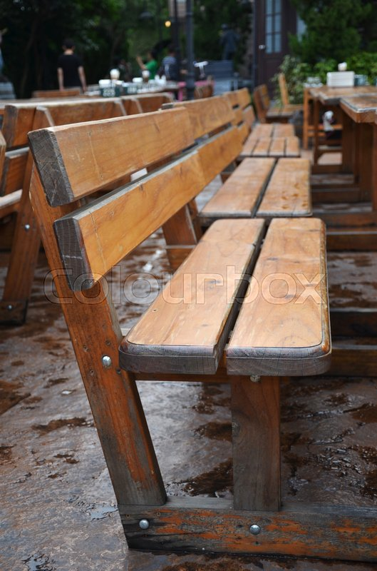 Stock image of 'Wooden long bench in outdoor dinning area '
