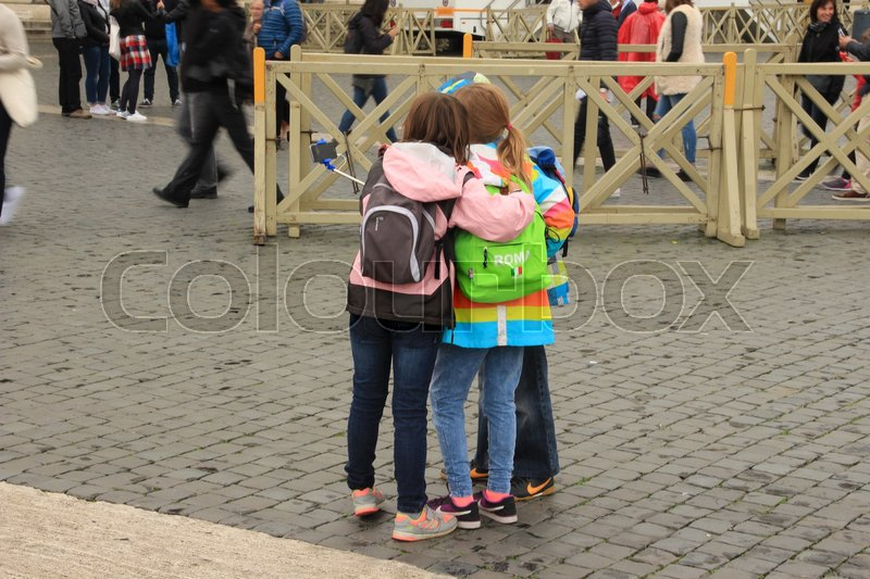 Stock image of 'The schoolboy and the two schoolgirls in striking raincoats making a selfie in one of the streets in the city Rome in Italy in the summer.'