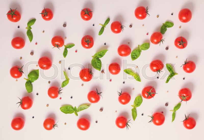 Stock image of 'Top view of beautiful trendy pattern cherry tomato, dry peppers and basil lives on pink background, flat design, close up'