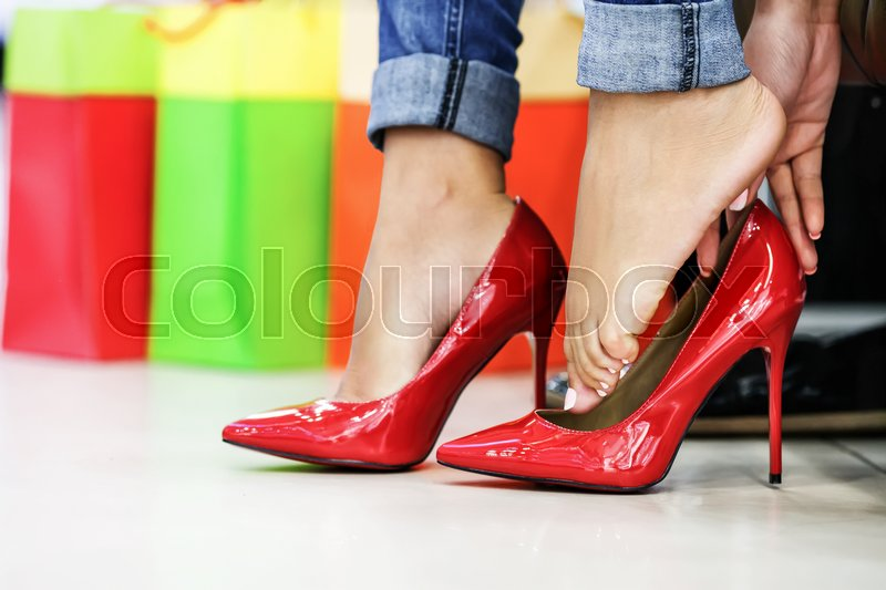 Stock image of 'Close up of woman fitting red elegant stilettos'