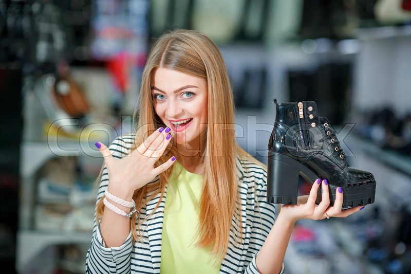 Stock image of 'Extcited woman holding a black boot in the shoe store'