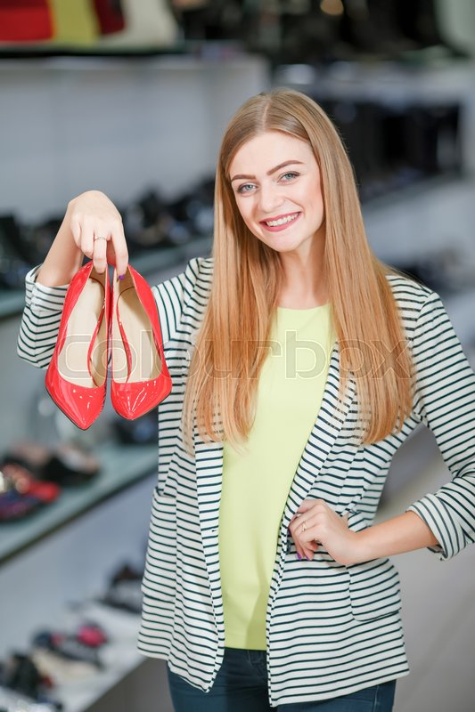 Stock image of 'Happy woman holding red high-heeled shoes in the shoe store'