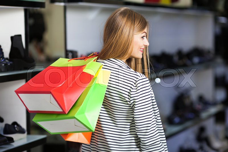 Stock image of 'Happy woman with bags in shoe store'