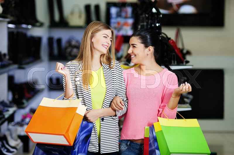 Stock image of 'Two young smiling women shopping in the shoe store'