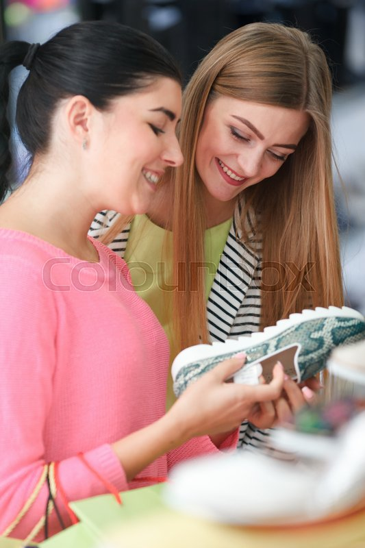Stock image of 'Two young women choosing shoes in the shoe store'