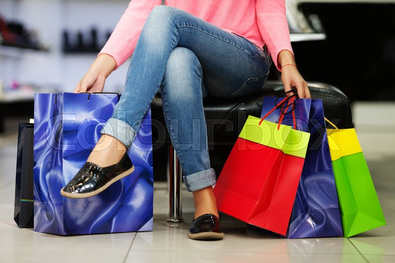 Stock image of 'Close up of woman's legs sitting with many shopping bags'