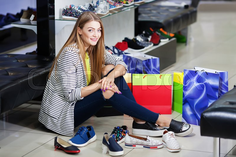 Stock image of 'Young woman sitting on the floor in the shoe store choosing shoes'