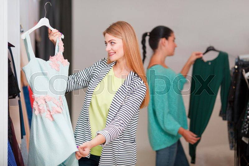 Stock image of 'Two women shopping, one is excited holding a cute dress'
