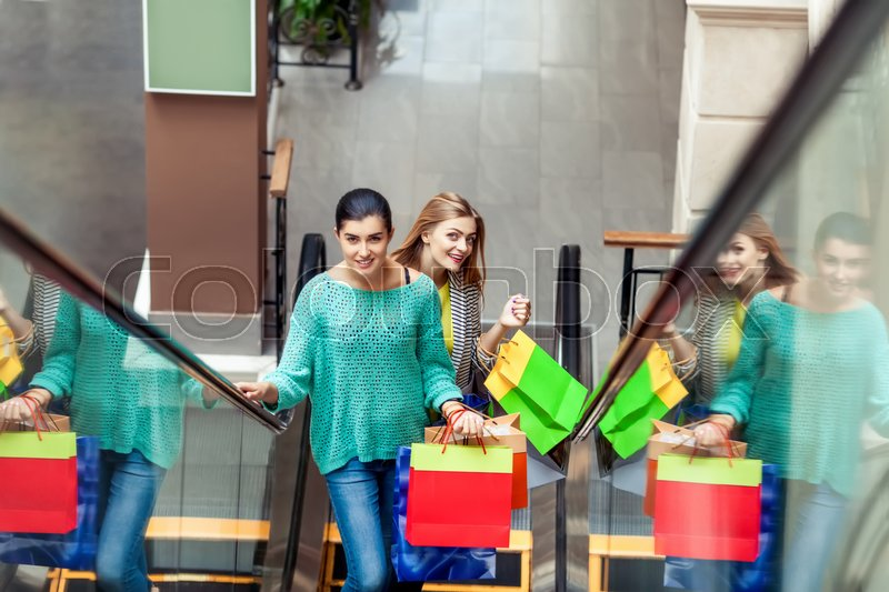 Stock image of 'Women on the moving staircase holding bags after shopping'