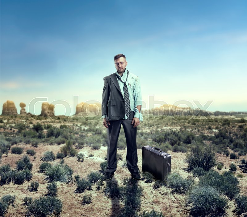 Stock image of 'Injured businessman with suitcase in savanna'