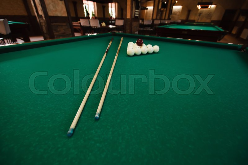 Stock image of 'Billiard balls and pool sticks on the green table'