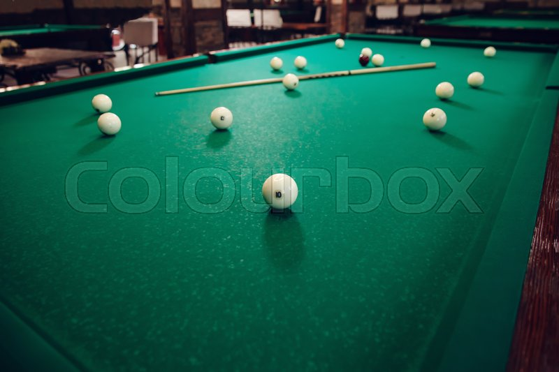 Stock image of 'Billiard able with balls and stick on it'