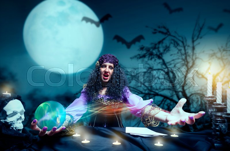 Stock image of 'Angry sorceress working with crystal ball'