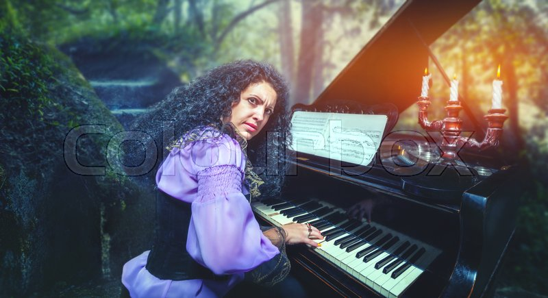 Stock image of 'Mystic woman playing the piano in the forest'