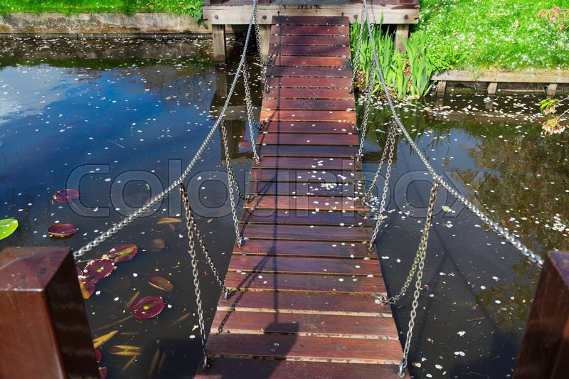 Stock image of 'Wooden Bridge over river in spring garden'
