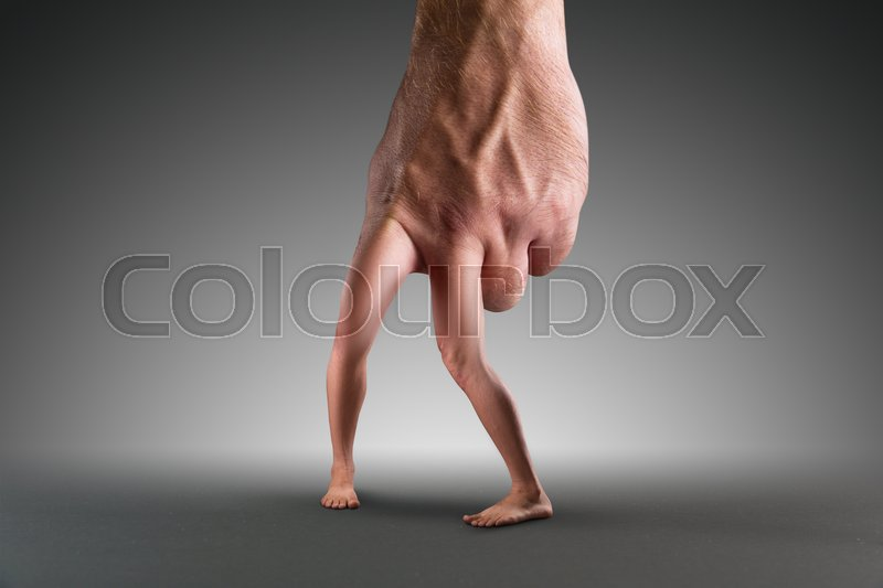 Stock image of 'Male hand with legs instead of fingers over grey'