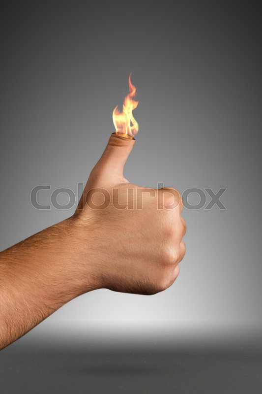 Stock image of 'Burning thumb up over grey background'