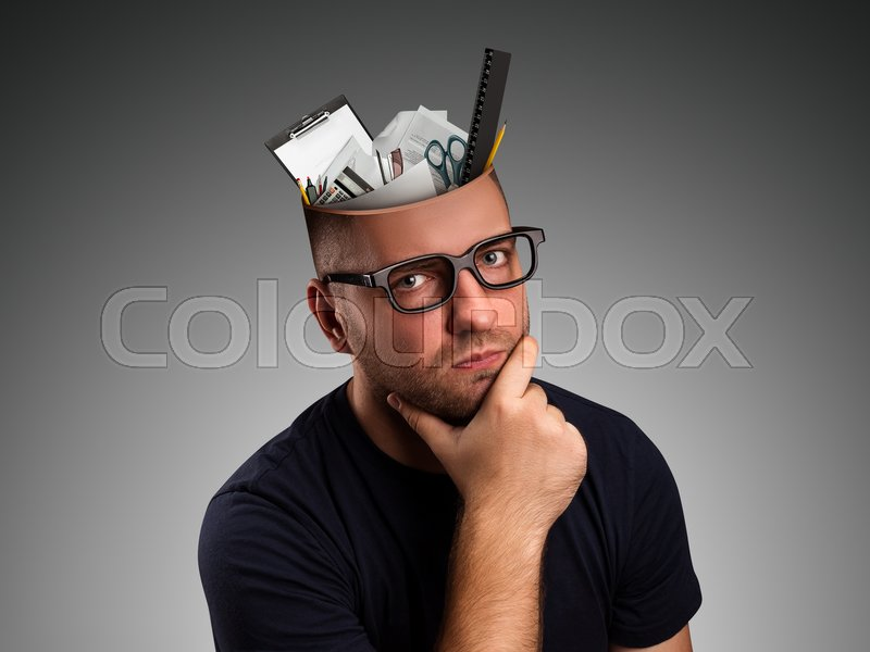 Stock image of 'Pensive man with office details in the head over grey'
