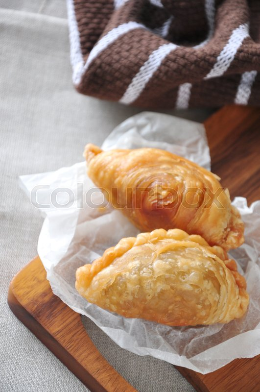 Stock image of 'Top view of two curry puff on wooden board'
