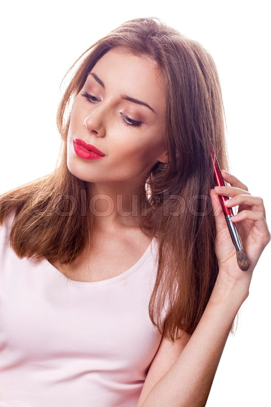 Stock image of 'Close up portrait of attractive caucasian brunette woman isolated on white studio shot, looking at camera brush makeup'