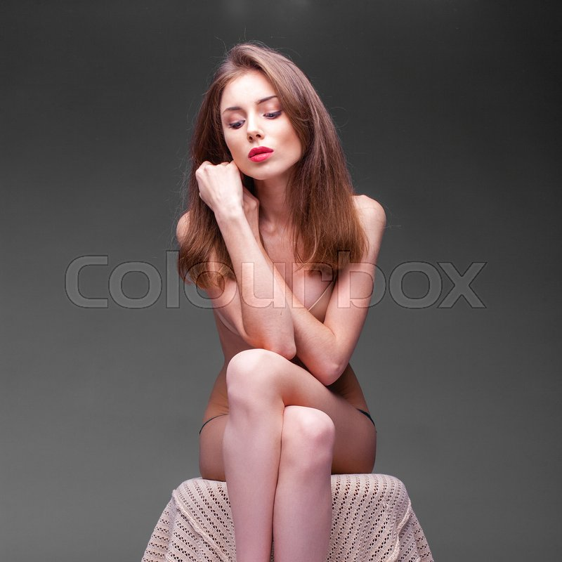 Stock image of 'Young beautiful naked woman sitting in the dark studio'