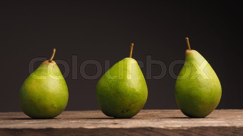 Stock image of 'Three delicious green pears on a wooden table'