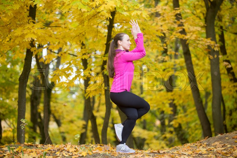 Stock image of 'Sporty beautiful smiling young woman practicing yoga, standing in Eagle Pose, Garudasana, working out outdoors in autumn park wearing bright sportswear. Full length, side view'