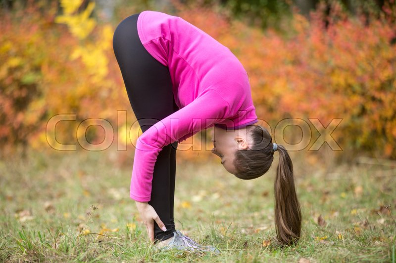 Stock image of 'Sporty beautiful young woman practicing yoga, doing uttanasana, intense stretch pose, Standing forward bend or head to knees pose, working out outdoors on autumn day. Full length, side view'
