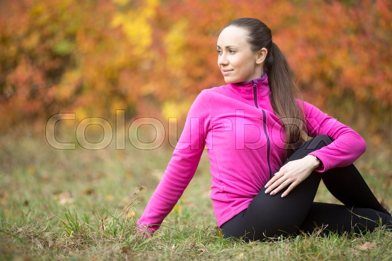 Stock image of 'Sporty beautiful young woman practicing yoga, sitting in Vakrasana, variation of Half lord of the fishes pose, Ardha Matsyendrasana, working out outdoors on autumn day. Side view. Copy space'