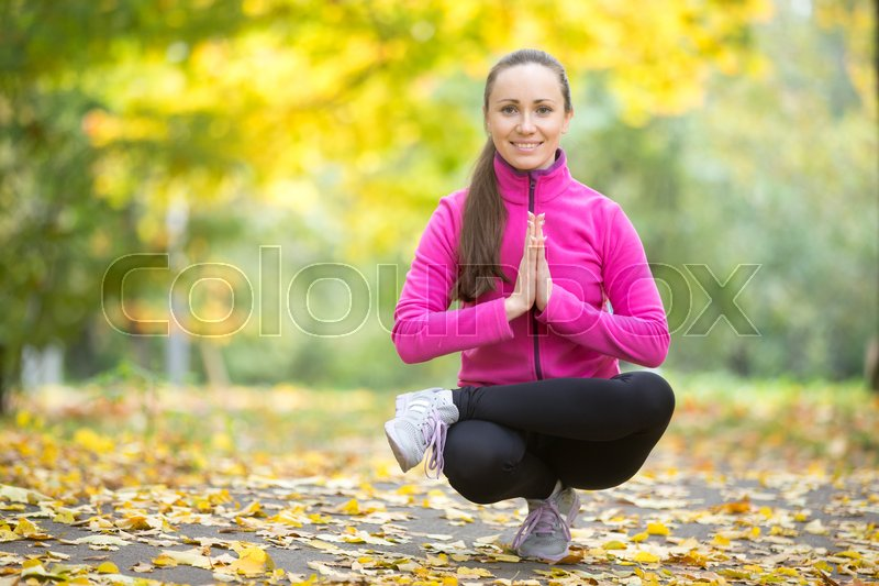 Stock image of 'Beautiful young sport woman practicing yoga, sitting in squat, Half Lotus Toe Balance, variation of Utkatasana, working out outdoor on autumn day wearing bright sportswear, full length'