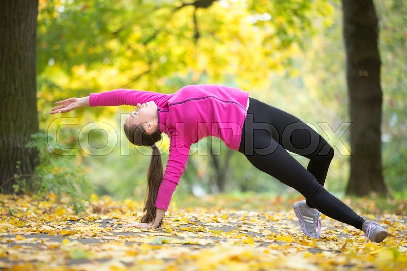 Stock image of 'Sporty beautiful young woman practicing yoga, standing in Camatkarasana, Wild Thing or Flip-the-Dog posture, doing everyday morning routine, working out outdoors on autumn day. Full length'