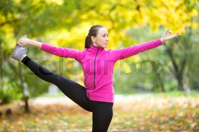 Stock image of 'Portrait of sporty beautiful happy young woman practicing yoga, standing in Utthita Hasta Padangustasana, Extended Hand to Big Toe pose, working out outdoor on autumn day wearing sportswear sweatshirt'