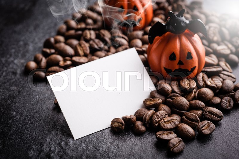 Stock image of 'Halloween pumpkin decoration with coffee beans on dark background'