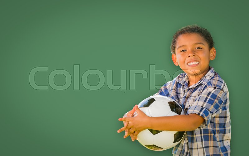 Stock image of 'Cute Smiling Young Mixed Race Boy Holding Soccer Ball In Front of Blank Chalk Board.'
