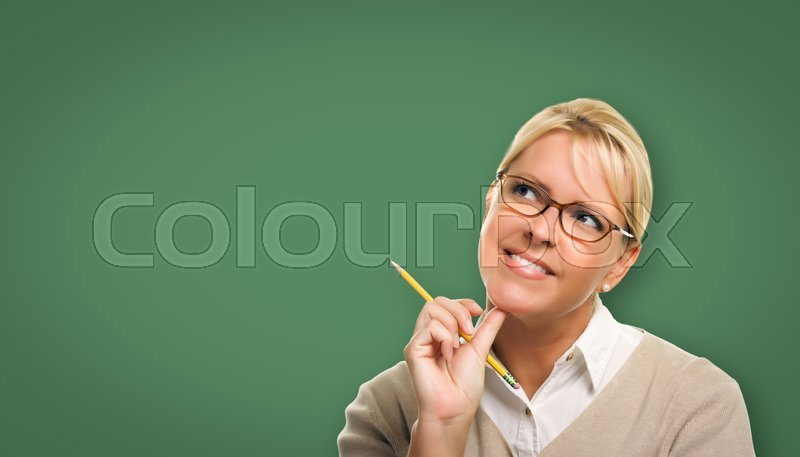 Stock image of 'Attractive Young Woman with Pencil and Glasses In Front of Blank Chalk Board.'