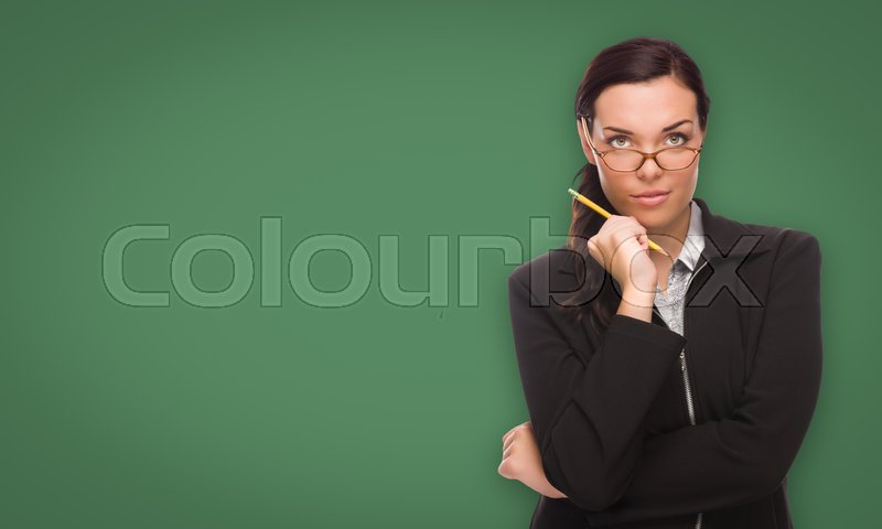 Stock image of 'Serious Young Woman with Pencil and Glasses In Front of Blank Chalk Board.'