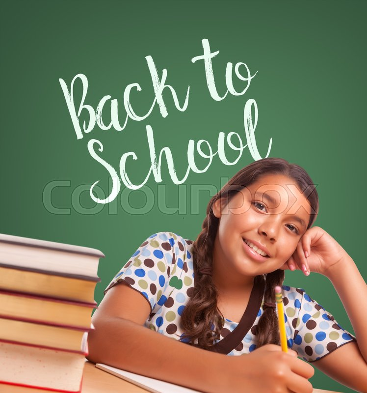 Stock image of 'Cute Smiling Hispanic Girl Studying In Front of Back To School Written on Chalk Board.'