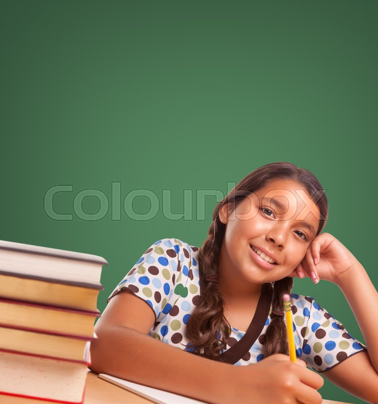 Stock image of 'Cute Smiling Hispanic Girl Studying In Front of Blank Chalk Board.'