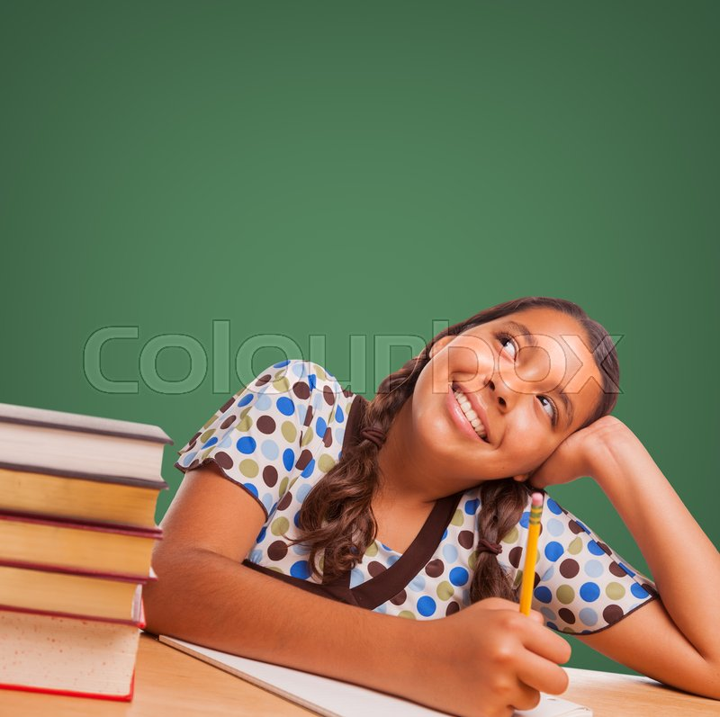 Stock image of 'Cute Hispanic Girl Studying and Looking Up to Blank Chalk Board.'