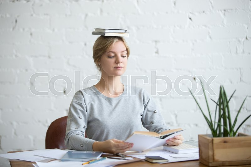 Stock image of 'Portrait of a young attractive woman at the desk with books on her head, sitting straight, reading a book. Education concept photo, lifestyle'